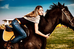 On a horseback. Young blond woman in blue jeans on a horseback, late summer day royalty free stock photos