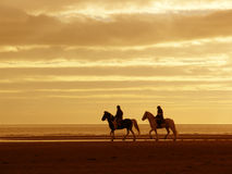 On Horseback. Two horseriders riding on a beach against a background of sea and sky Royalty Free Stock Photography