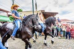 Horseback cowboy & veedrijfster in dorp, Guatemala Stock Afbeelding
