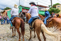 Horseback cowboys ride in village, Guatemala Royalty Free Stock Photos