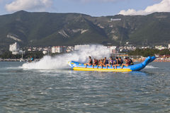 Horseback on an inflatable raft in Gelendzhik Bay. Driver of motorcycle aqueous drenches water attraction participants. Beach reso Stock Image