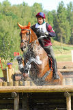 Horseback jumping in water drops royalty free stock images