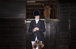 Horseback Rider With Horse And Dog. Young female horseback rider with horse and dog in the stable Royalty Free Stock Photo