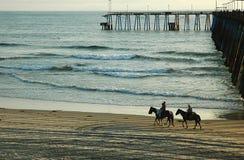 Horseback riders. Horseback riding on the beach stock photo