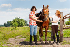 Horseback riders having rest with their bay horse. Happy horseback riders having rest with their beautiful bay horse after walking outback in summer Royalty Free Stock Images