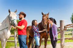 Horseback riders having rest with their horses. Three horseback riders having rest with their horses, standing next to the fence of the paddock at sunny day Stock Photos
