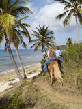 Horseback Riders By The Ocean. Two teenage girls on a trail ride through the palm tree down to the ocean on the tropical island of St. Croix, US Virgin Islands Royalty Free Stock Image
