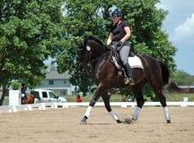 Horseback riding. Woman riding black Hanoverian Warmblood on cloudy day Royalty Free Stock Photo