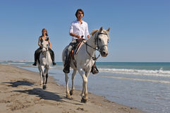 Horseback riding on the beach. Father and daughter are riding with their white horses on the beach Royalty Free Stock Photos