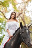 Horseback riding. Beautiful young woman in a white dress riding on a brown horse outdoors. Royalty Free Stock Images