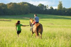 Horseback Riding Lessons - Woman Leading a Horse with a Boy in S Royalty Free Stock Photo