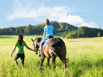 Horseback Riding Lessons - Woman Leading a Horse with a Boy in S Stock Image