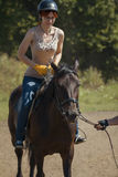 Horseback riding lessons - young woman riding a horse Stock Image