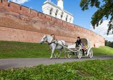 Horseback riding near the wall of Novgorod kremlin Stock Photos