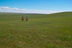 Horseback ruiters in weide Royalty-vrije Stock Afbeeldingen
