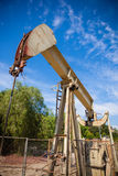 Horsehead pumpjack with a blue sky background Royalty Free Stock Image