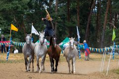 Horseman acrobat with bow on the running horses. Horseman stunt with bow on the 4 horses during a horse track contest and horse show in Romania Royalty Free Stock Photos