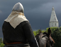 Horseman in armor on a background of church and stormy sky Stock Photo