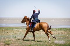 Horseman in blue military clothes riding along the seashore with a sabre in his hand royalty free stock images