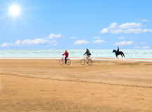 Horseman and cyclists. On a beach Stock Photography