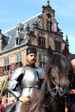 Horseman dressed in suit of armour. During a medieval event in the historical dutch city of Nijmegen. At the background a historical building. Gebroeders van Royalty Free Stock Images
