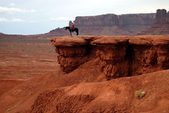 Horseman at John Ford Point, Monument Valley, Arizona. Man with white cowboy hat riding a black horse, on a sandstone cliff at John Ford point in Monument Valley Royalty Free Stock Photo