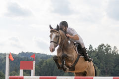 Horseman in jump over the obstacle closeup Stock Photo