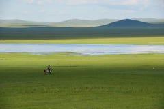 Horseman and prairie. A horseman with a horse pole ride on the prairie along a river Stock Photo