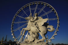Horseman statue on the Place de la Concorde with ferris wheel in  Paris, France Royalty Free Stock Image