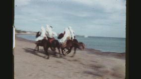 Horsemen Charging By The Beach. TUNISIA, GABES REGION, WINTER 1973. Two Shots Sequence With Pan Of Horsemen In Traditional Outfits Showing Off Their Riding stock video