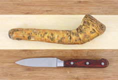 Horseradish root on cutting board with knife Royalty Free Stock Photography