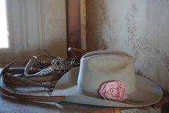 Horses belts, hat with flower, cowboys style. Horses belts, beige hat color with pinck flower, cowboys and cowgirls style, western, on table stock photos