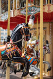 Horses on a carnival Merry Go Round. Old French carousel in a holiday park. Big roundabout at fair in amusement park. Royalty Free Stock Photo
