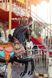 Horses on a carnival Merry Go Round. Old French carousel in a holiday park. Big roundabout at fair in amusement park. Stock Images
