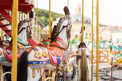 Horses on a carnival Merry Go Round. Old French carousel in a holiday park. Big roundabout at fair in amusement park. Stock Photography