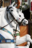 Horses of a carousel in amusement park Stock Images