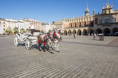 Horses and carriage at Old Town Krakow, Poland. KRAKOW, POLAND - SEPTEMBER 14, 2017: Horse-drawn carriage in Krakow`s Old Town square is a popular attraction for Royalty Free Stock Image