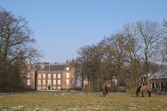 Horses in front of castle. A black and a brown horse on a frozen paddock in front of an ancient manor. To the right and in the back are the farm buildings and Stock Image