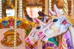 Horses on a fun fair merry go round carousel Stock Image