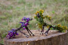 Horses, made of branches and flowers. Horse made of twigs and flowers. Yellow and purple flowers Stock Photo
