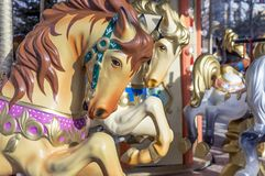 Horses on the old children`s circular carousel stock images