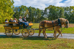 Horses Pull Wagon at Landis Valley. Lancaster, PA, USA - October 9, 2016:  Visitors ride in a horse-drawn wagon at the Landis Valley Farm and Museum during the Stock Photo