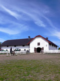 Horses' stud farm. Beautiful view of the horses' stud farm with white fence and two riders in the paddock stock photos