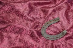 Horse shoe on a red textile background stock photos