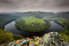 Horseshoe bend, Vltava river, dark clouds with autumn leaves on the rock, Solenice, Czech republic Stock Image