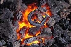 Horseshoe. Blacksmithing, heating of the metal horseshoes on coals Royalty Free Stock Photos