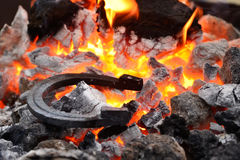 Horseshoe in the coals and flames royalty free stock photography