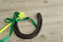 A horseshoe displayed with a four leaf clover. And a green bow for St. Patrick's day stock images
