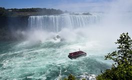 HORSESHOE FALLS NIAGARA FALLS. Horseshoe Falls can be seen from the Canadian side as a boat takes tourists out. Goat Island can be seen in the distance stock photos
