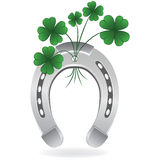 Horseshoe and four leaf clover Stock Photography